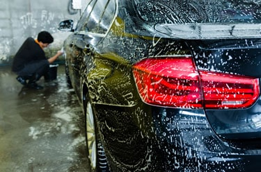person is cleaning car